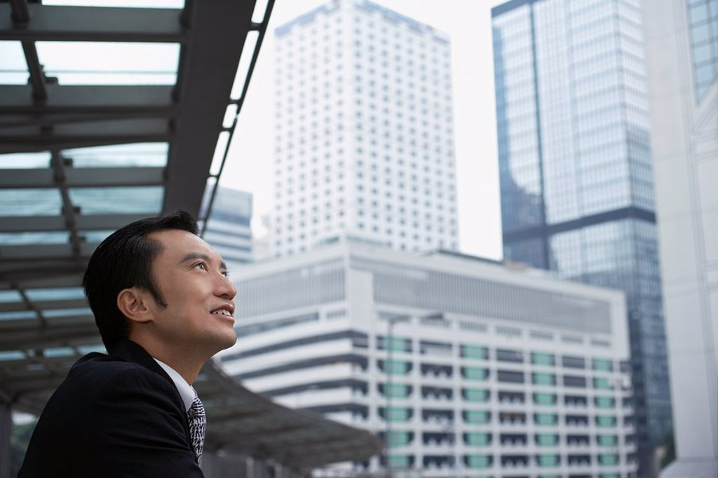 China Hong Kong business man looking at cityscape side view : Stock Photo