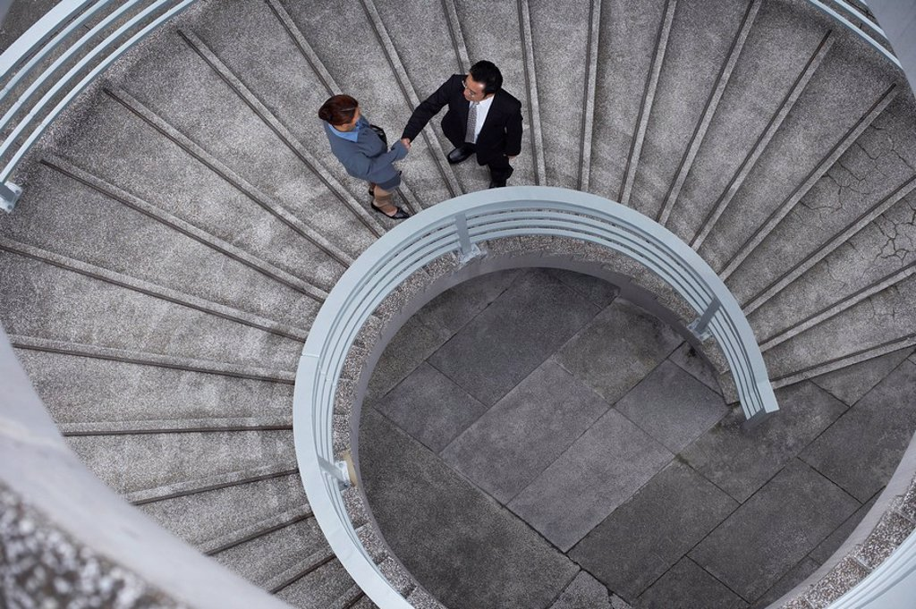 Stock Photo: 1654R-24495 China Hong Kong two business people shaking hands standing on spiral staircase view from above