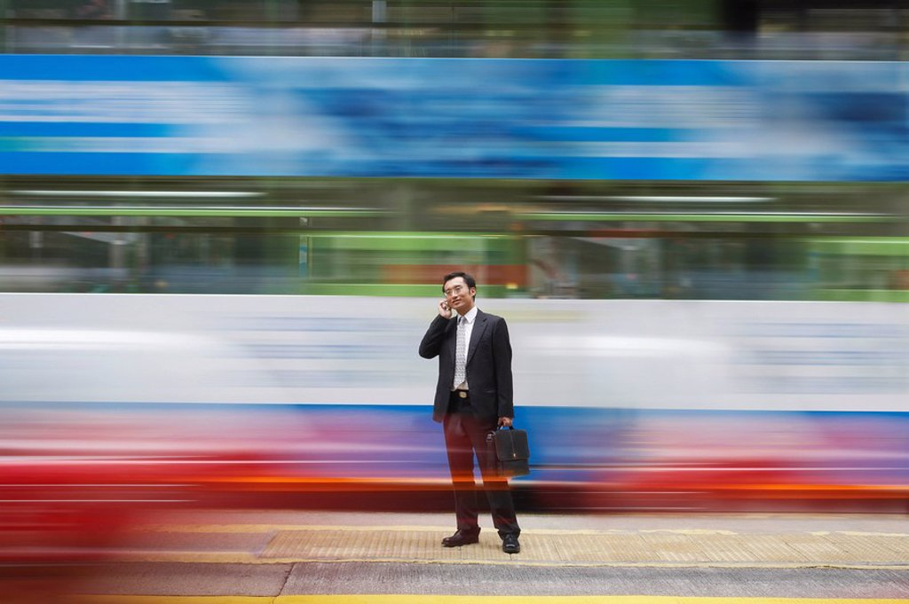 China Hong Kong business man using mobile phone standing on street long exposure : Stock Photo