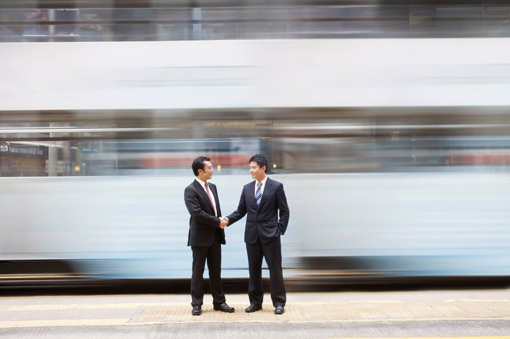 China Hong Kong two business man shaking hands standing on street crossing long exposure : Stock Photo