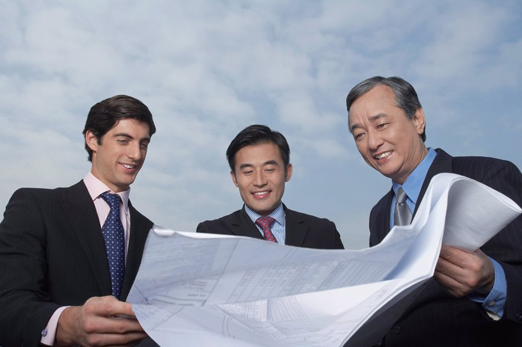 Three business holding and looking at blueprints smiling : Stock Photo