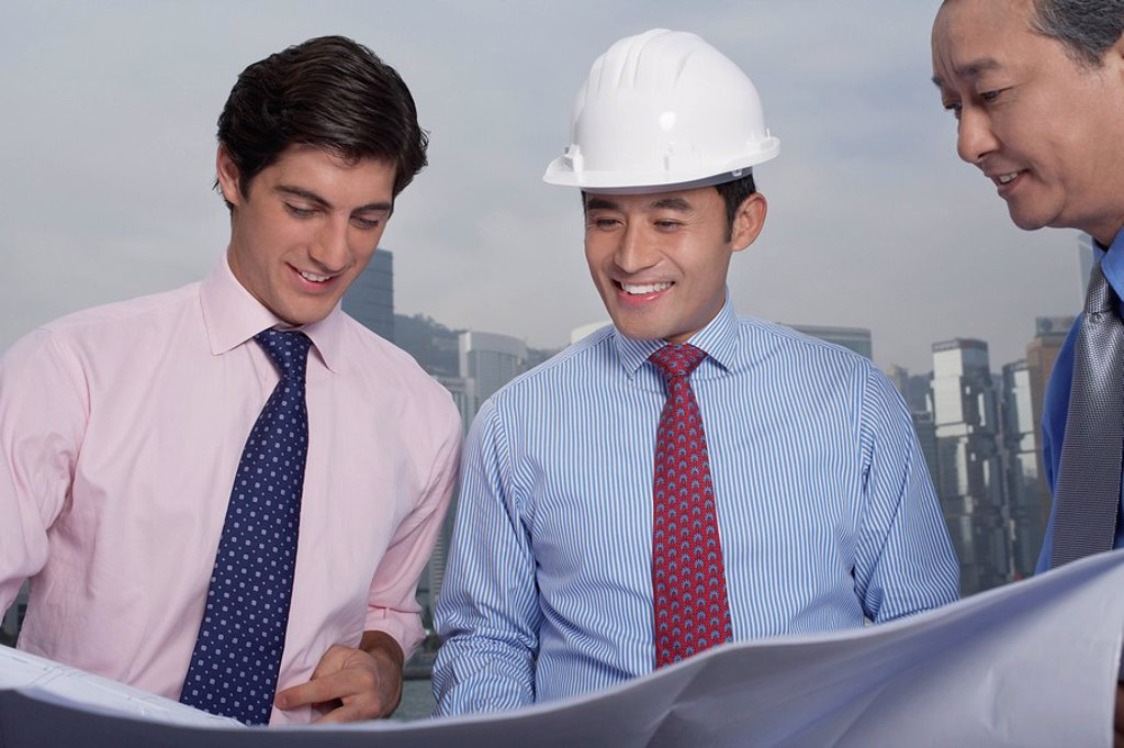 Business men and construction site manager reading blueprints : Stock Photo