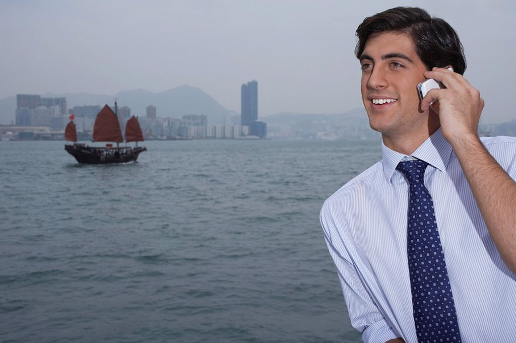 Young business man talking on mobile traditional Chinese junk boat in background : Stock Photo