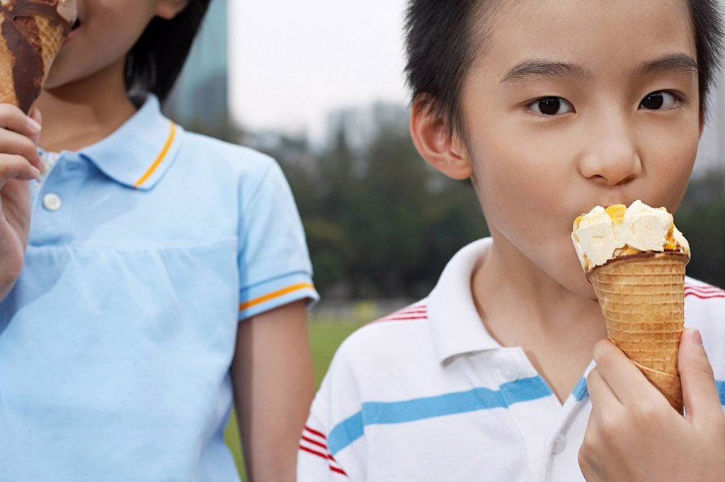 Boy and girl 7_9 eating ice cream close_up cropped : Stock Photo