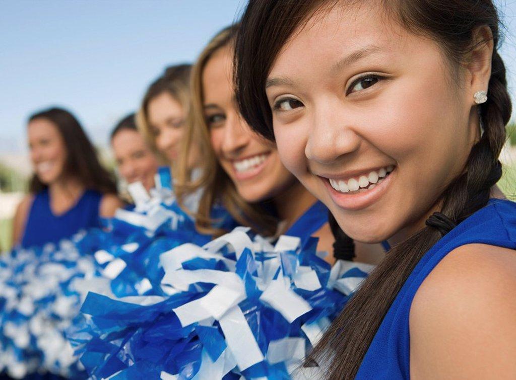 Cheerleaders sitting on bench portrait : Stock Photo