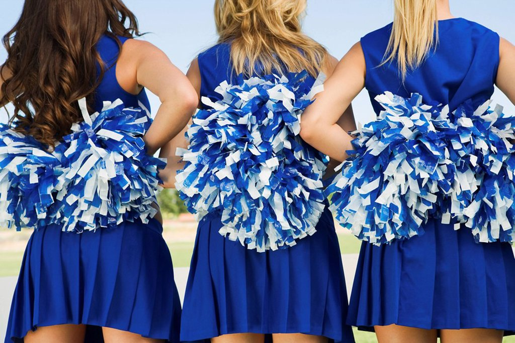 Cheerleaders holding pom_poms rear view mid section close_up : Stock Photo