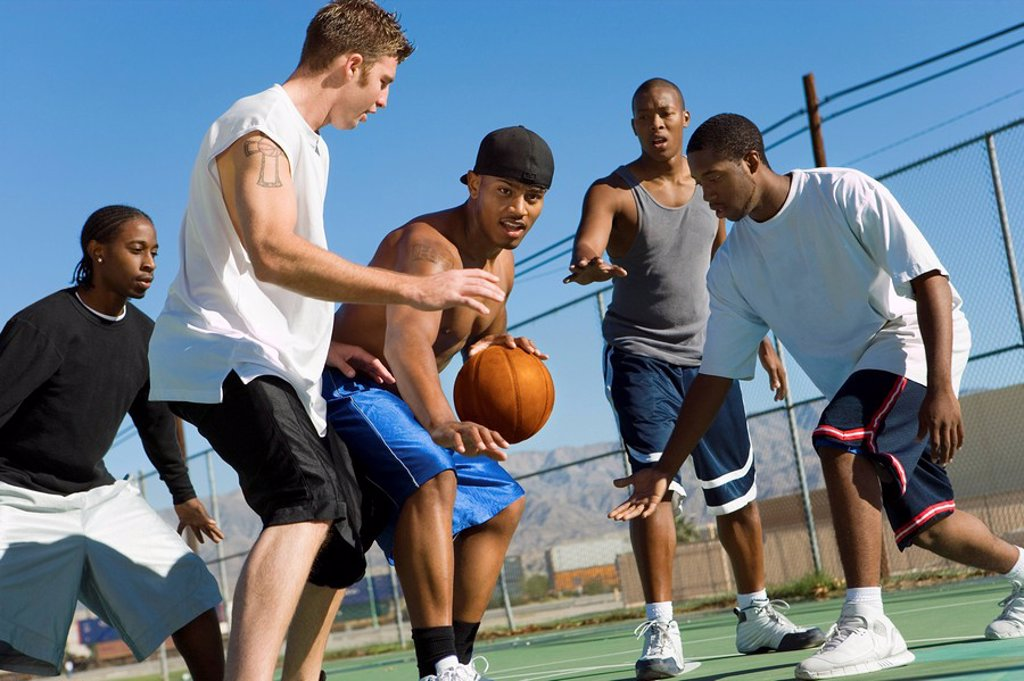 Young men playing basketball : Stock Photo