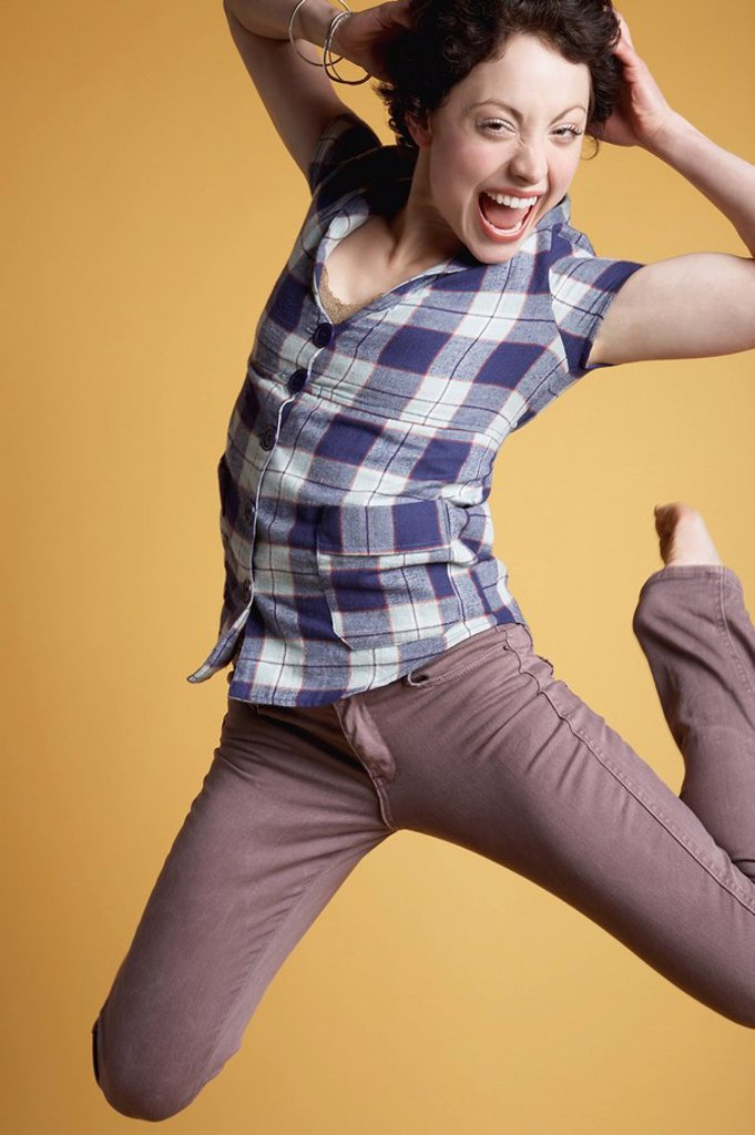 Stock Photo: 1654R-25129 Young woman jumping and screaming