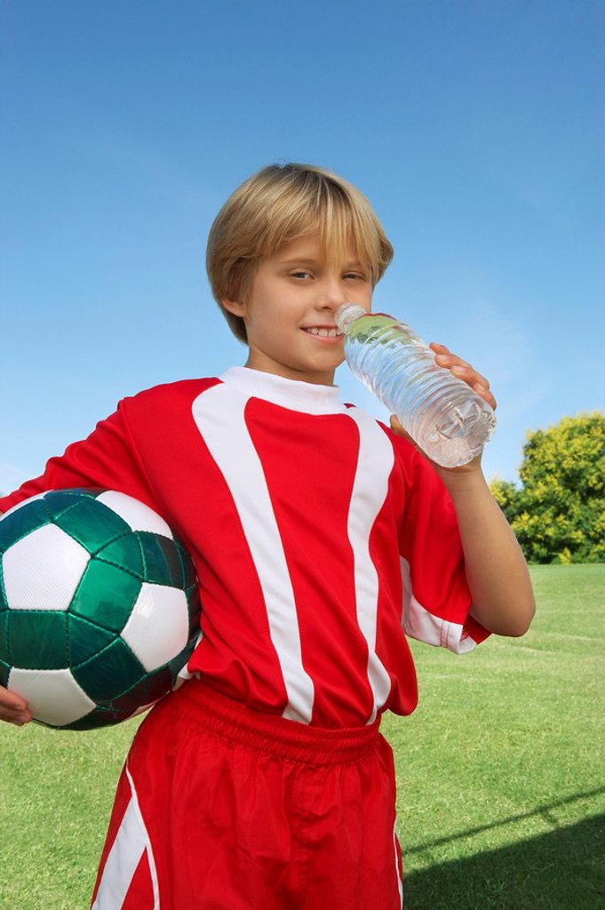 Boy 7_9 years soccer player holding ball and water bottle portrait : Stock Photo