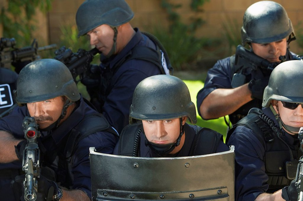Swat officers behind shield : Stock Photo