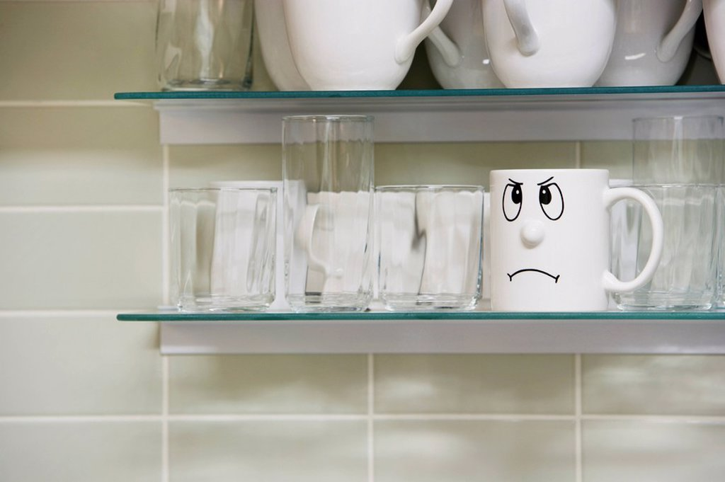 Sad face mug on kitchen shelf : Stock Photo
