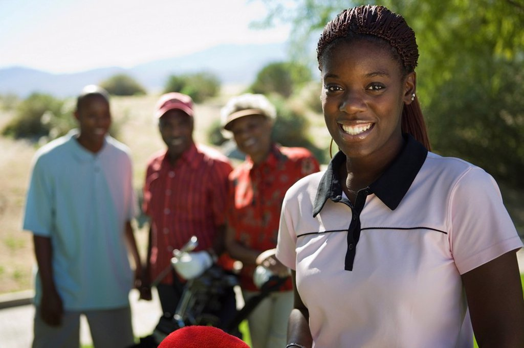 Stock Photo: 1654R-2602 Young woman on golf course portrait family in background