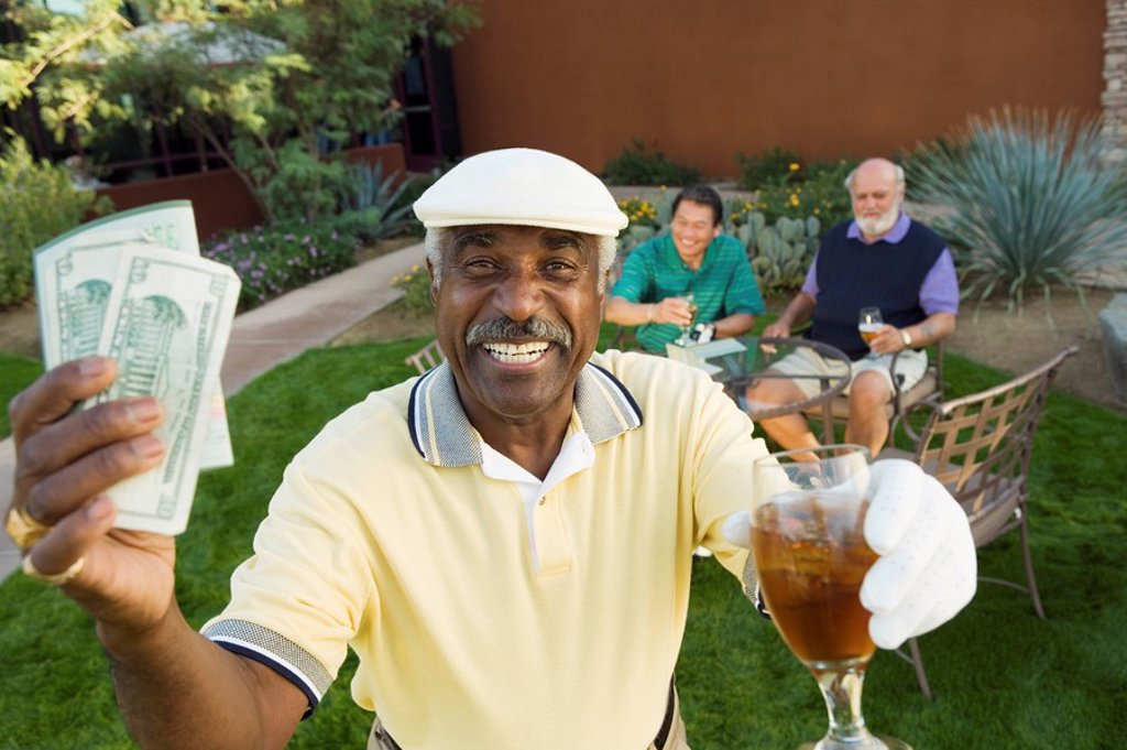 Senior golfers celebrating success focus on man showing banknotes portrait : Stock Photo