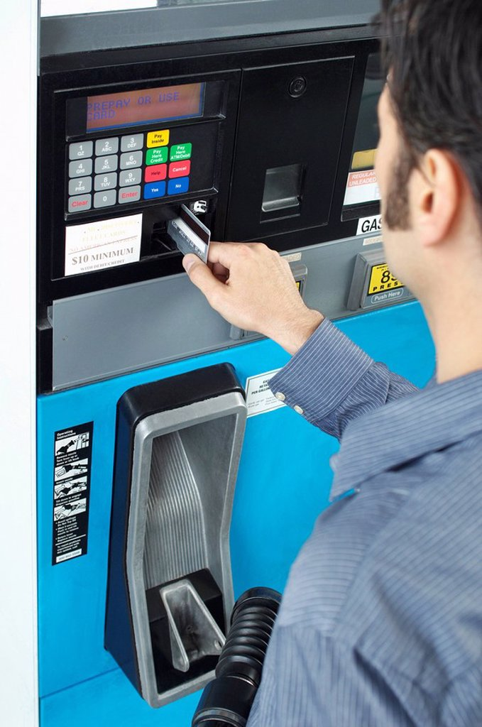 Man paying with credit card at fuel pump : Stock Photo