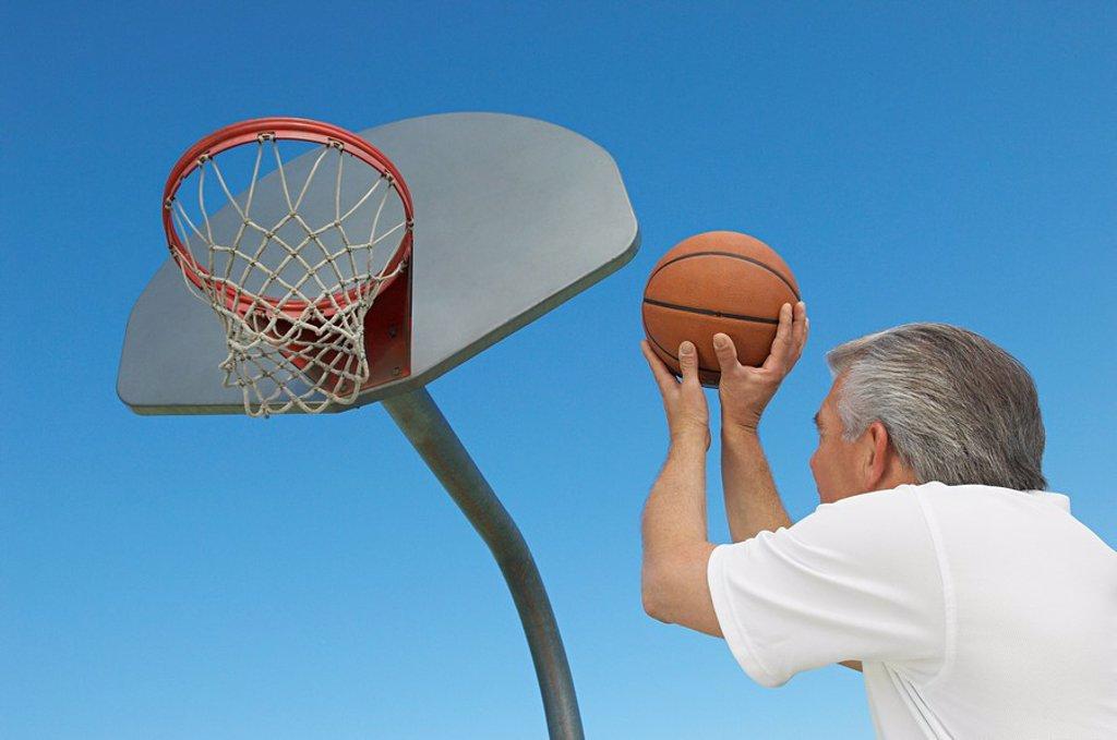 Senior man aiming basketball at hoop outdoors : Stock Photo