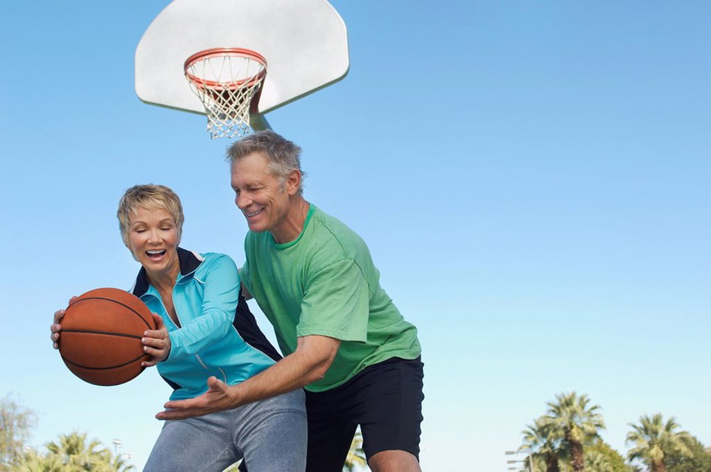 Stock Photo: 1654R-26547 Senior couple playing basketball on outdoor court