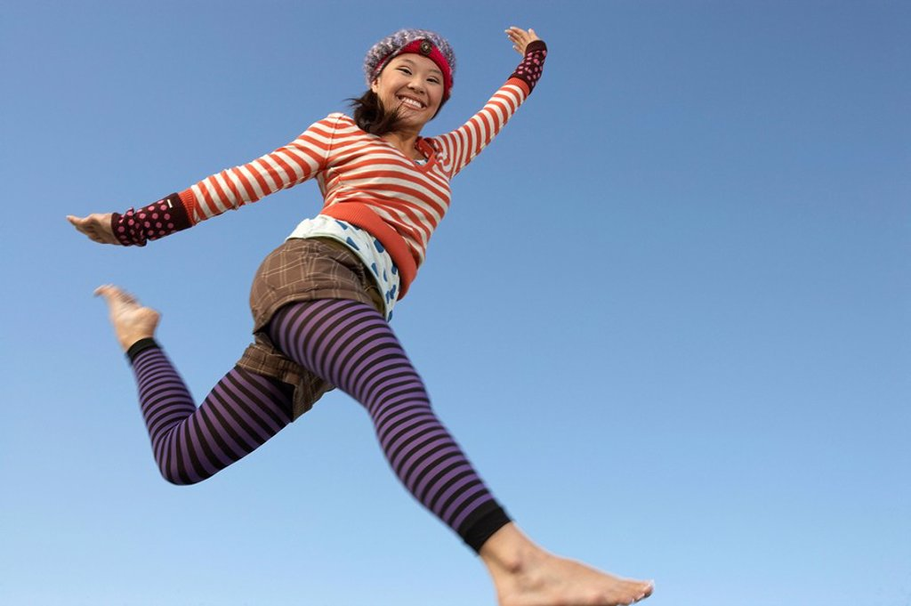 Stock Photo: 1654R-26598 Young woman jumping in striped outfit
