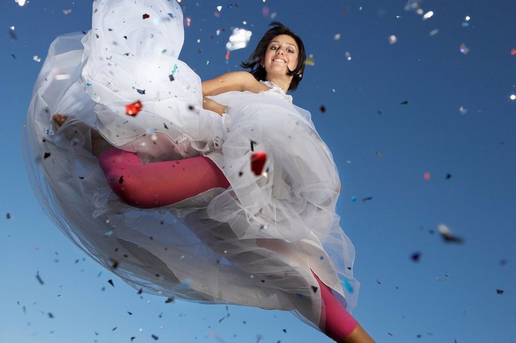 Portrait of young woman in wedding dress jumping : Stock Photo