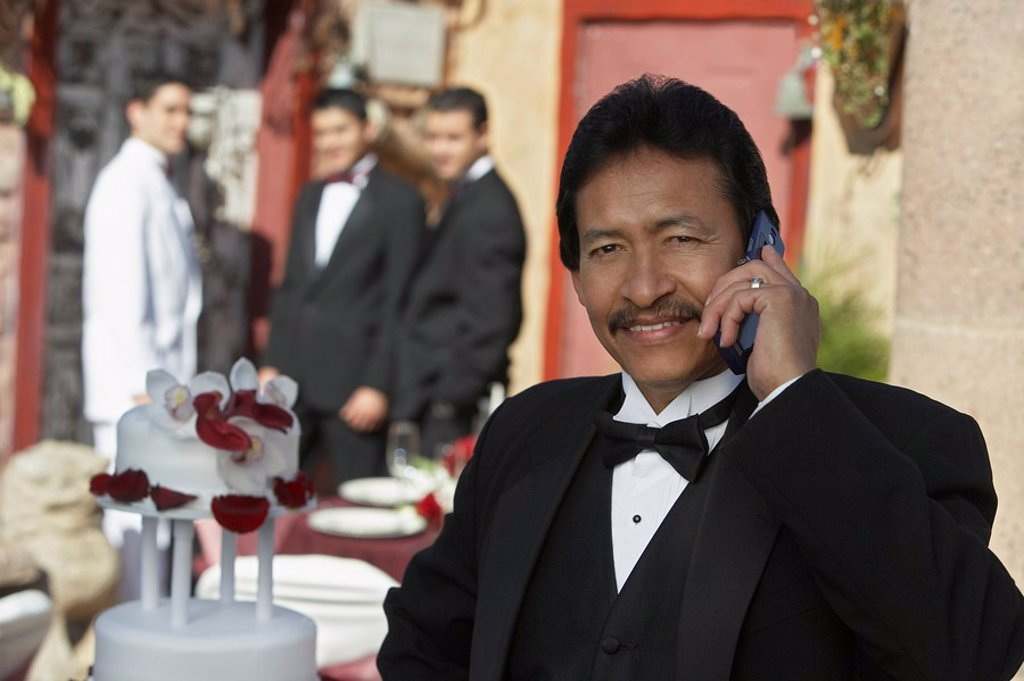 Man in tuxedo at Quinceanera using mobile phone : Stock Photo