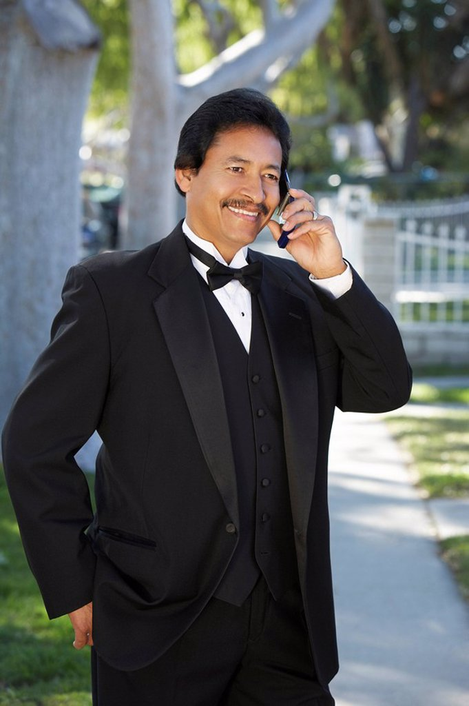Stock Photo: 1654R-26633 Portrait of man in tuxedo at Quinceanera using mobile phone