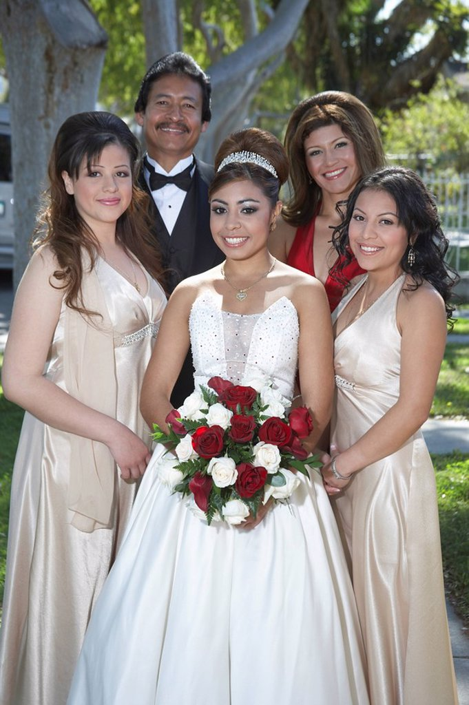 Portrait of girl 13_15 with parents and friends in garden at Quinceanera : Stock Photo