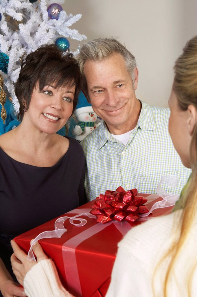 Woman handing senior couple present : Stock Photo