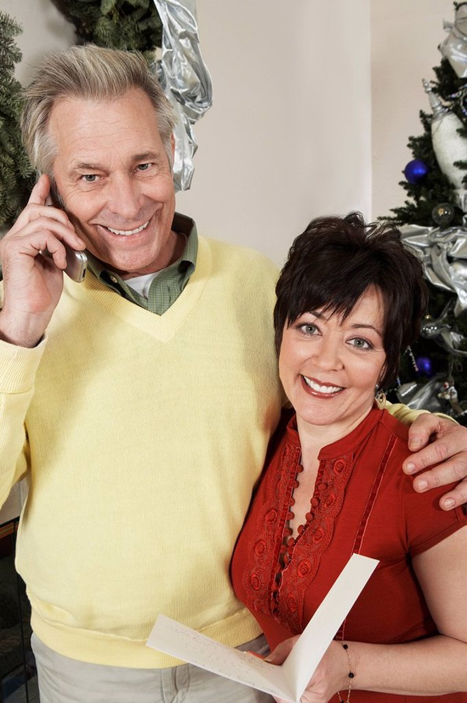 Senior couple holding greeting card man on cell phone : Stock Photo