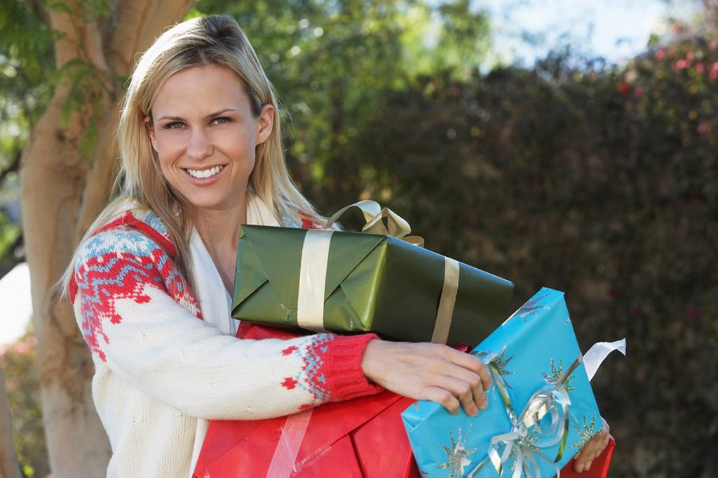 Woman carrying presents outside portrait : Stock Photo