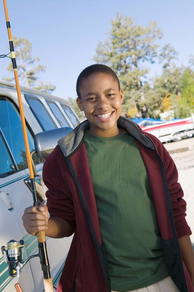 Boy holding fishing rod smiling portrait : Stock Photo