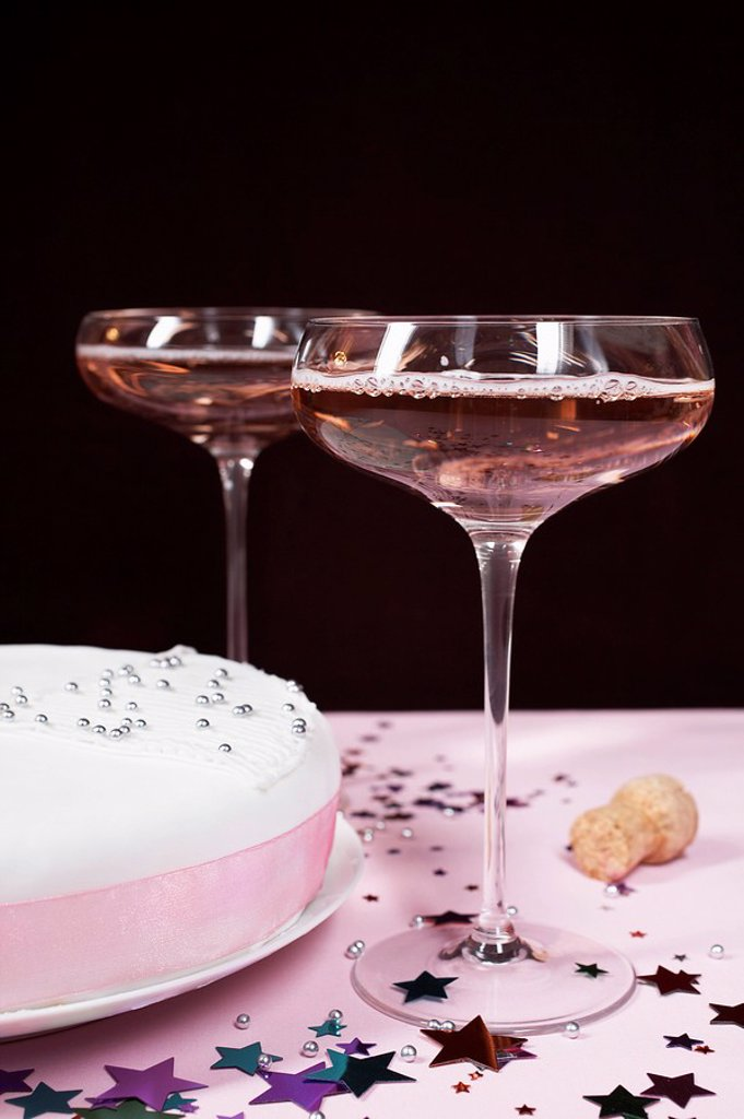 Two champagne glasses and cake close up : Stock Photo
