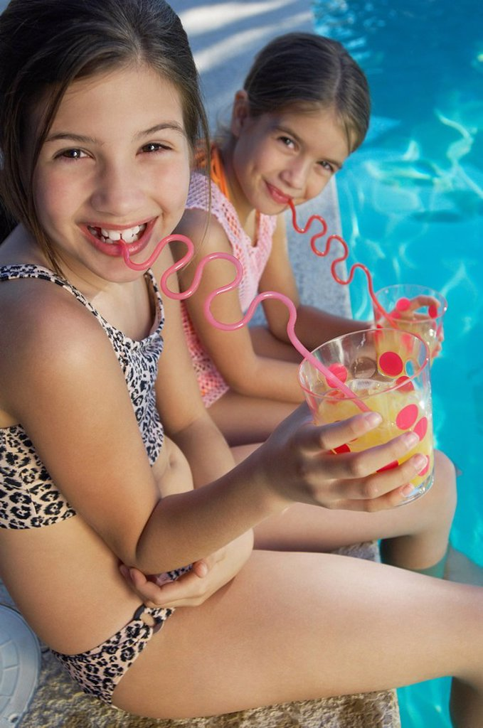 Stock Photo: 1654R-27738 Girls drinking juice from crazy straws on edge of swimming pool portrait