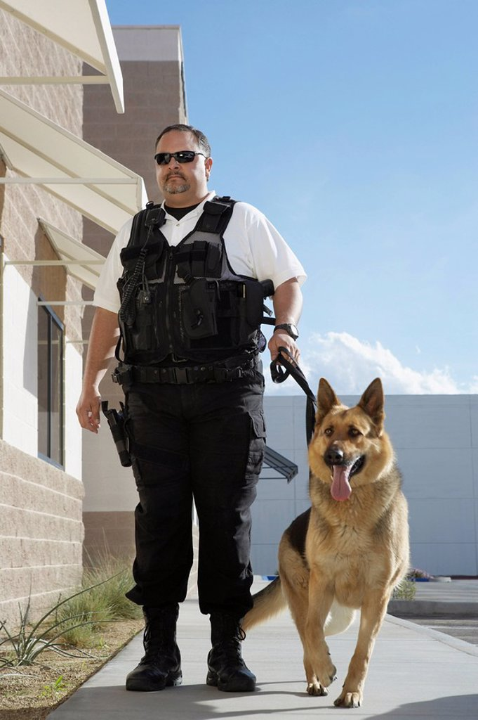 Stock Photo: 1654R-27885 Security guard with dog on patrol