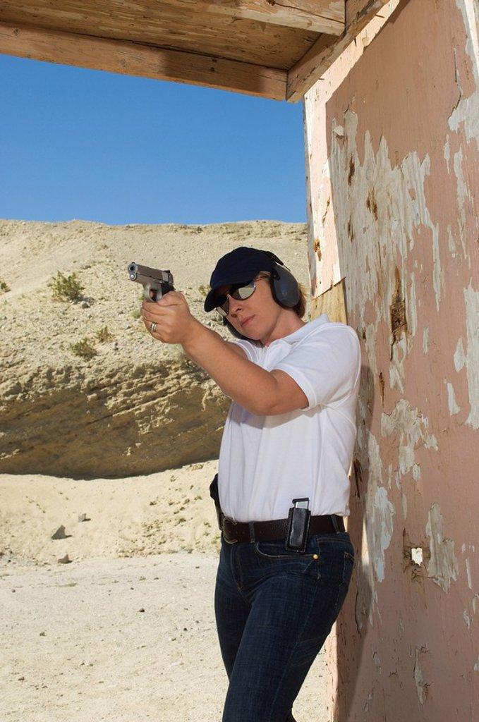 Stock Photo: 1654R-27994 Woman aiming hand gun at firing range