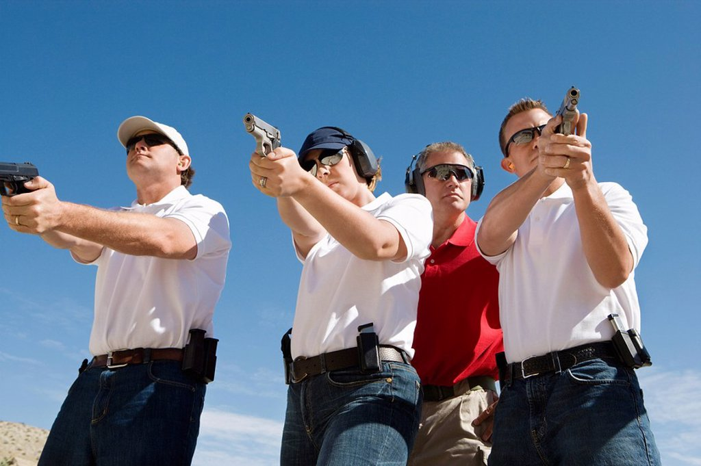 Stock Photo: 1654R-28045 Instructor assisting people aiming guns at firing range