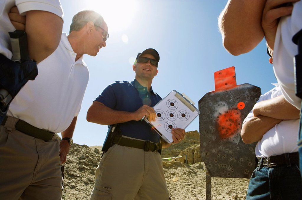 Instructor holding clipboard with target diagram at combat training : Stock Photo