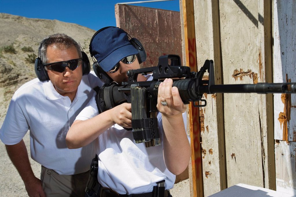 Instructor assisting woman aiming machine gun at firing range : Stock Photo