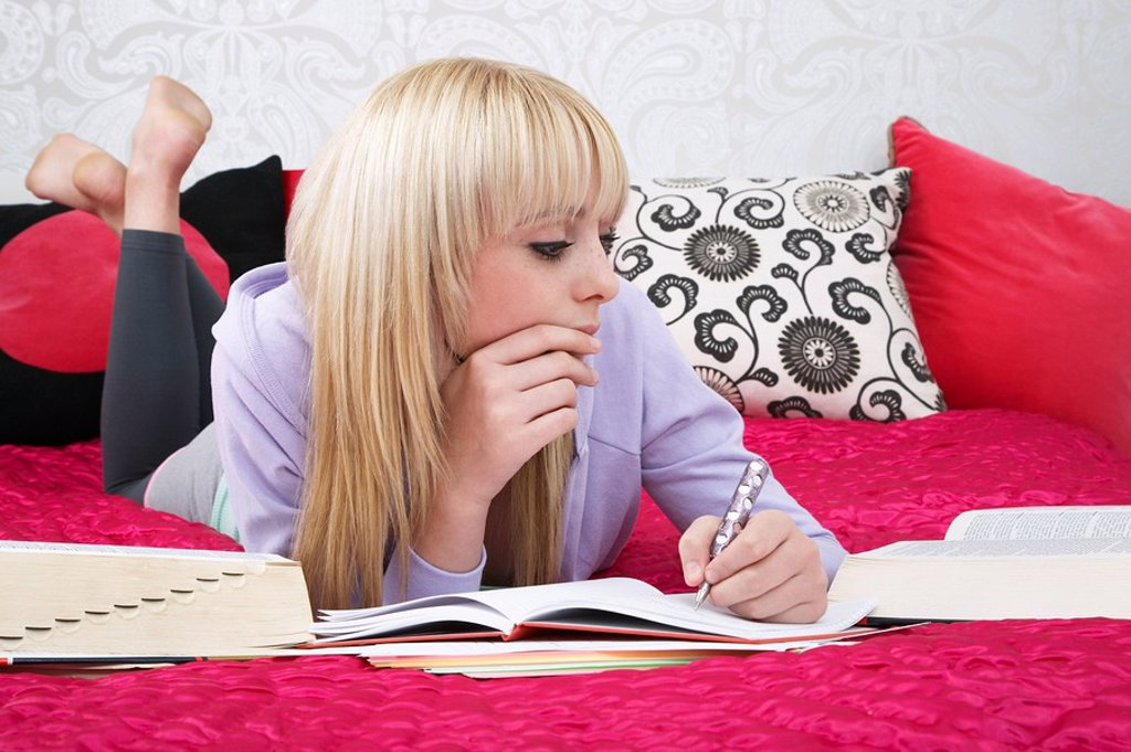 Teenage girl 16_17 lying on bed writing : Stock Photo