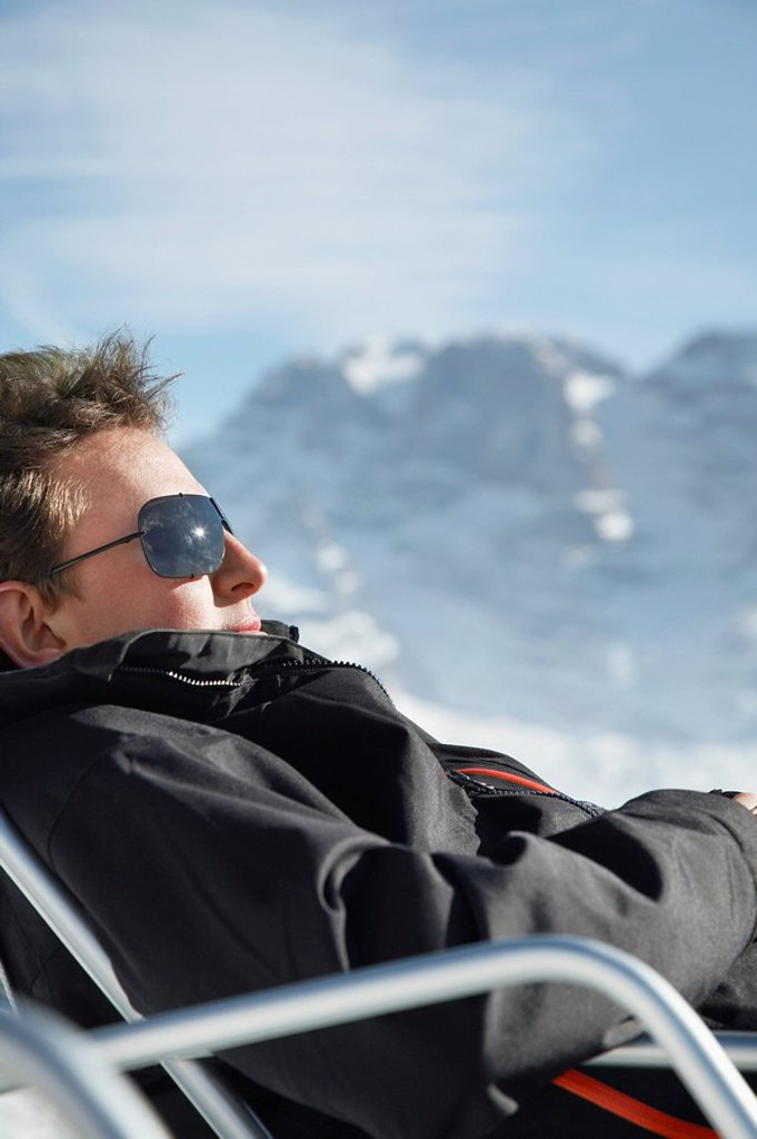 Stock Photo: 1654R-28334 Man in winter coat and sunglasses sitting in arm chair by mountains