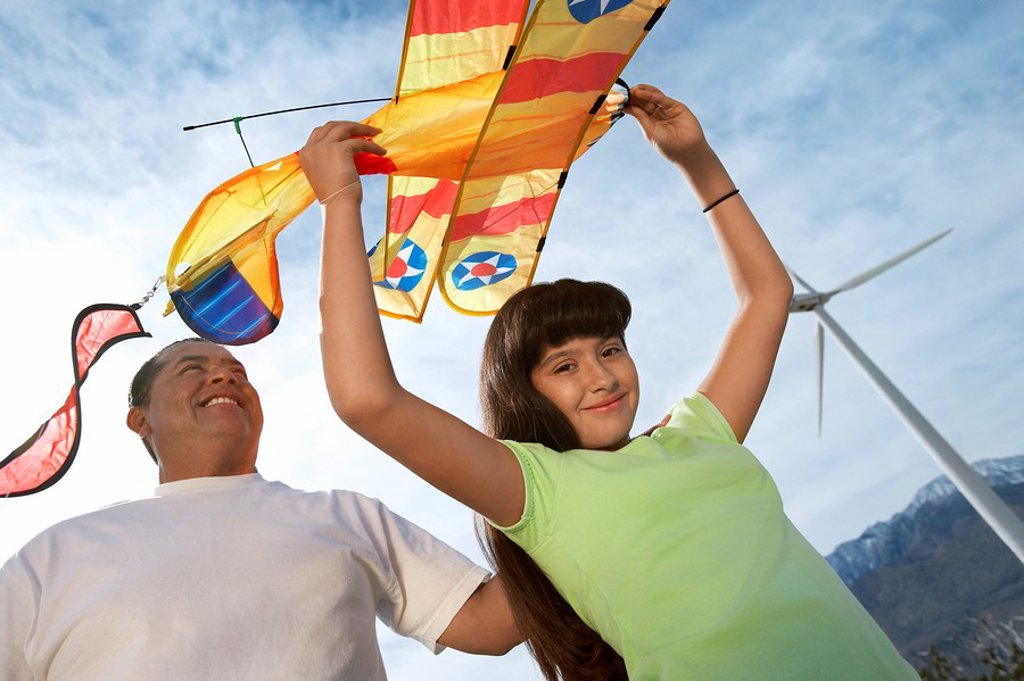 Girl 7_9 holding airplane kite with father at wind farm : Stock Photo