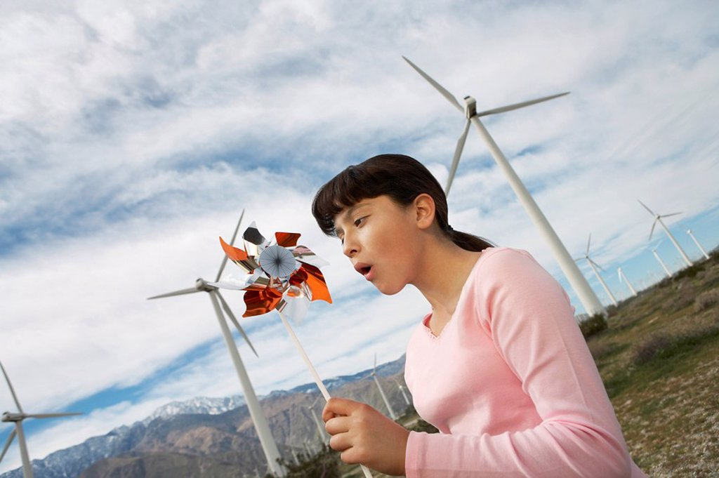 Stock Photo: 1654R-28945 Girl 7_9 playing with toy windmill at wind farm