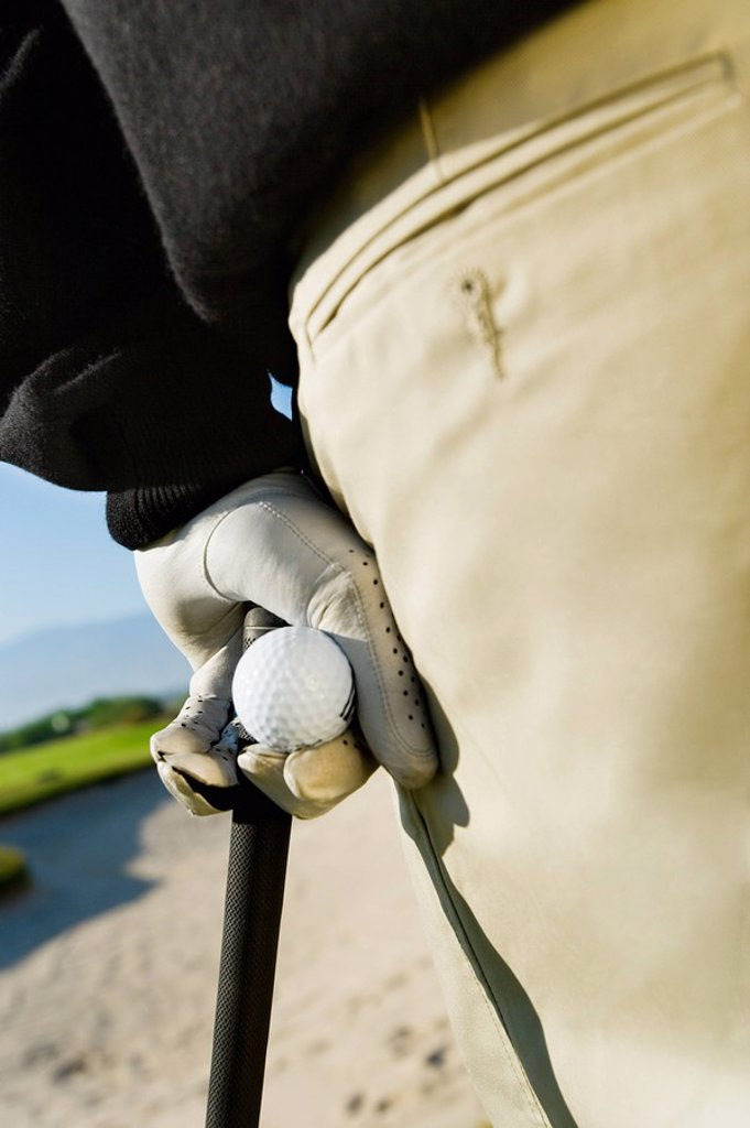 Golfer holding golf ball and club close_up : Stock Photo