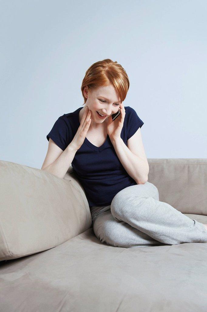 Woman talking on mobile phone on sofa : Stock Photo