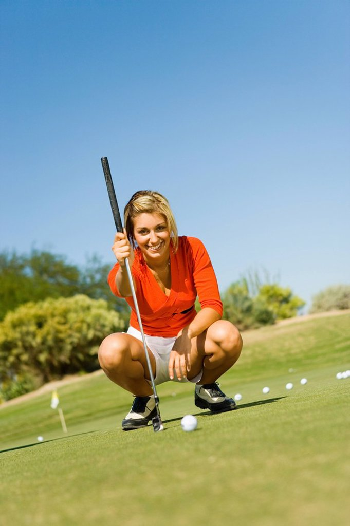 Female golfer lining up shot on putting green : Stock Photo
