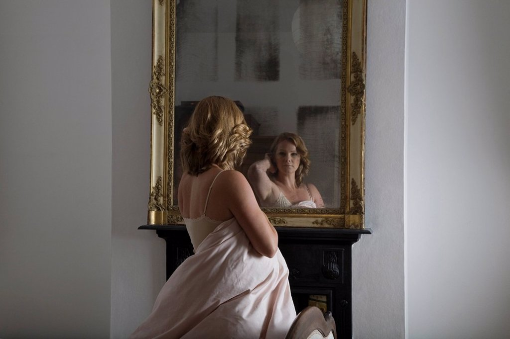 Stock Photo: 1654R-30930 Woman dressed in quilt examining herself in mirror