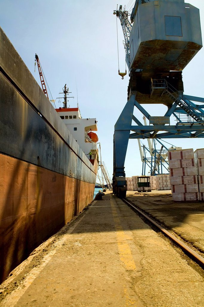 Limassol Cyprus. Crane loading a freighter with cargo on quayside : Stock Photo