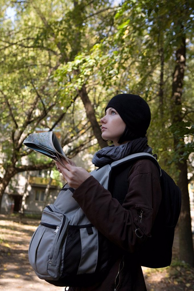 Young woman in winter clothes reading map : Stock Photo