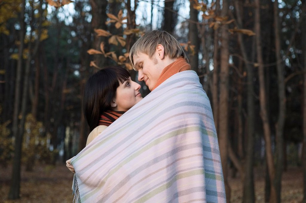 Young couple wrapped in blanket embracing in forest : Stock Photo