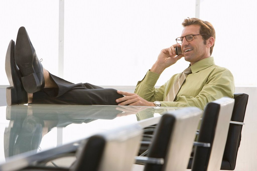 Business man using mobile phone in conference room : Stock Photo