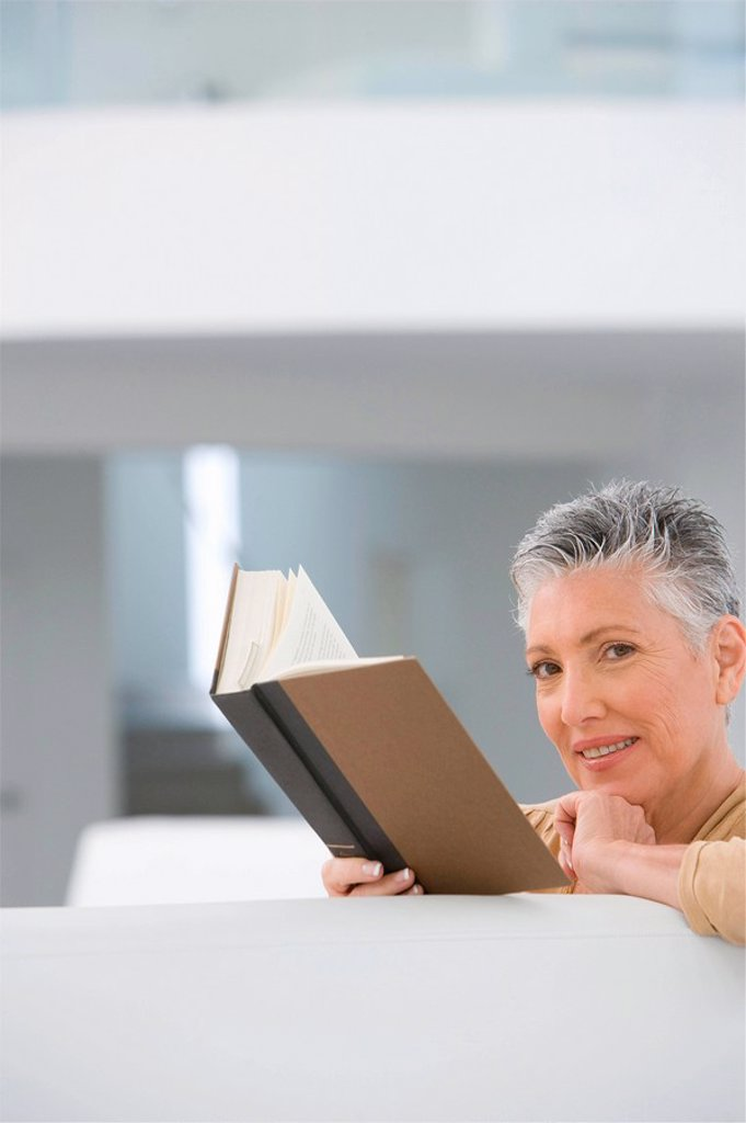 Middle_aged woman reading book on sofa : Stock Photo