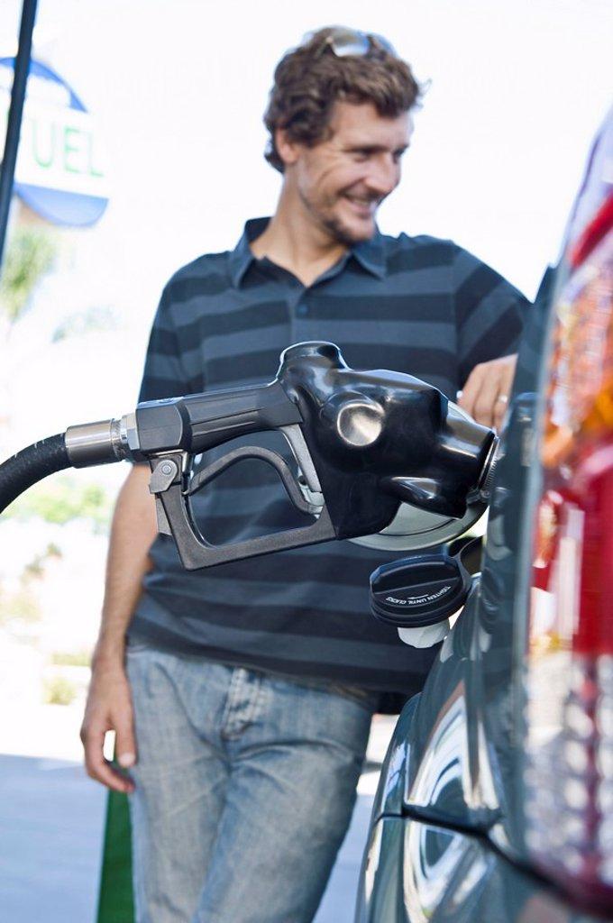 Smiling man refueling car at natural gas station : Stock Photo
